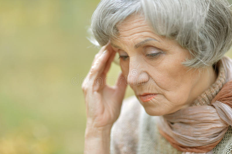 Sad old woman. Nice sad old woman on the autumn background royalty free stock images