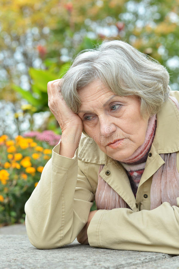 Sad old woman in park. Nice sad old woman on the autumn background royalty free stock images