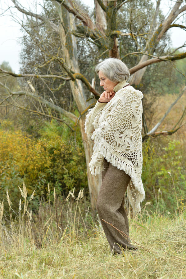 Sad old woman in park. Nice sad old woman on the autumn background stock image