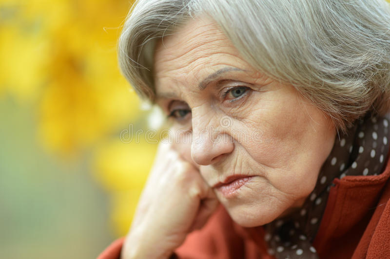 Sad old woman in park. Nice sad old woman on the autumn background royalty free stock photography