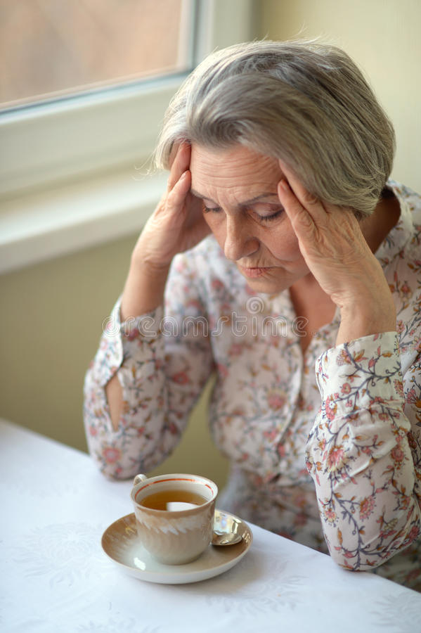 Sad old woman. Portrait of a sad old woman drinking tea royalty free stock photography