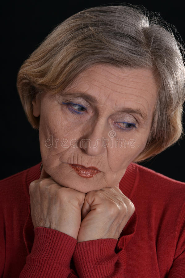 Sad old woman. In red on a black background stock images