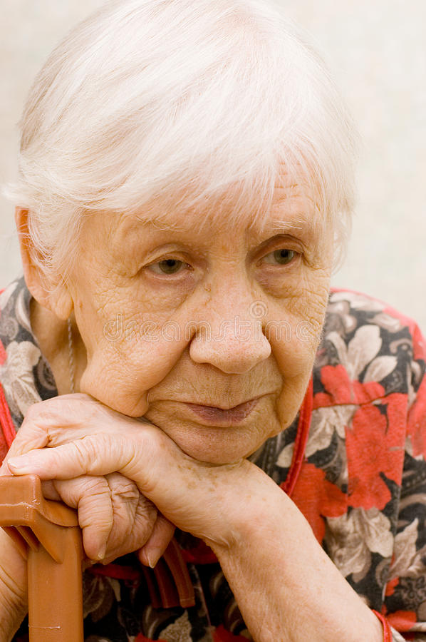 Sad old woman in a room. The sad old woman in a room royalty free stock photo