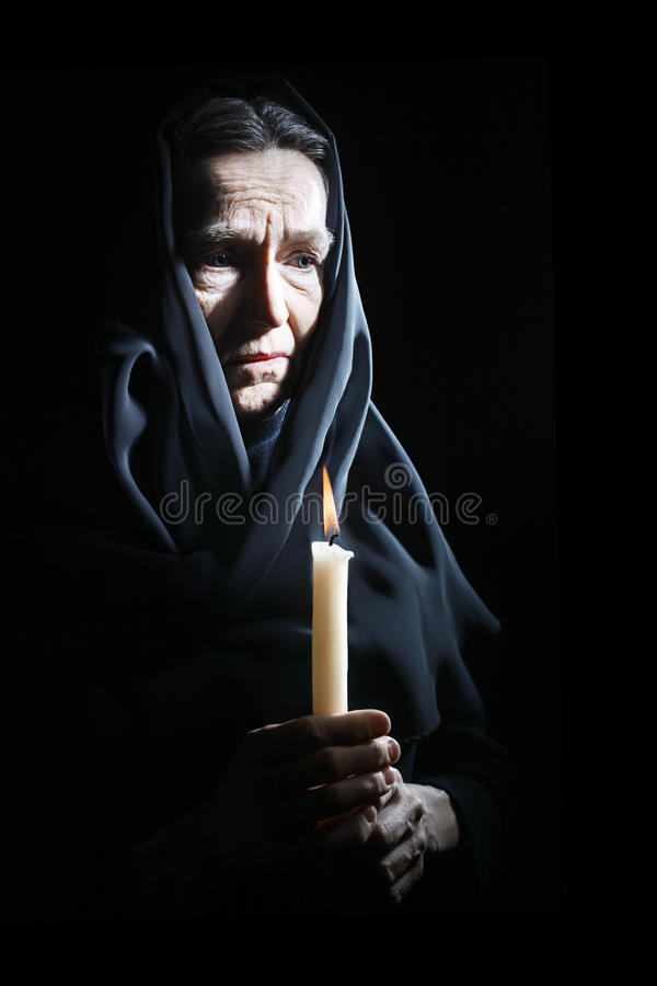 Sad old woman Senior in sorrow with candle. Sad old woman Senior woman in sorrow with candle depressed portrait royalty free stock photos