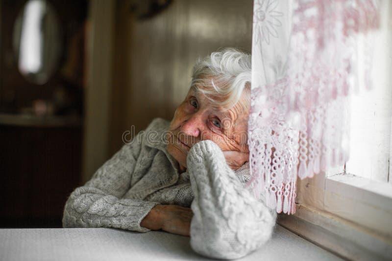 Sad old woman sitting near the window. Help. Sad old woman sitting near the window stock photo