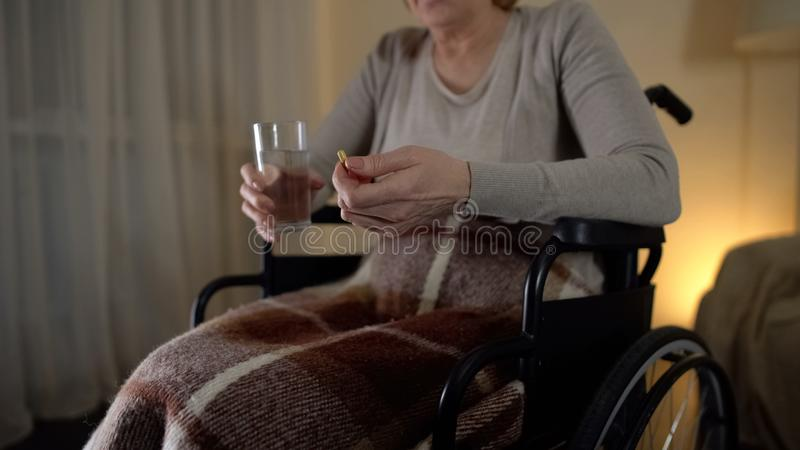 Sad old woman in wheelchair taking medicine, recovery period, depression. Stock photo royalty free stock image