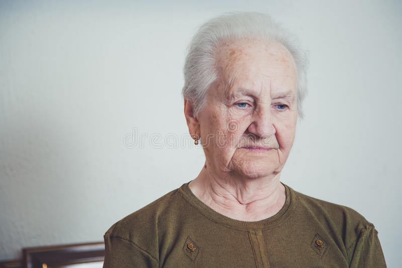 Sad older woman. Sitting in her house stock photo