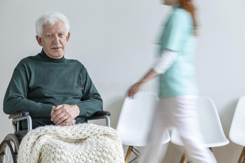 Sad paralyzed elderly man in the wheelchair in the nursing house. Sad paralyzed elderly men in the wheelchair in the nursing house. Motion of doctor stock image