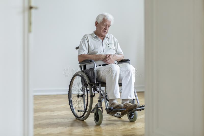Sad paralyzed senior man in the wheelchair sitting alone at home stock photography