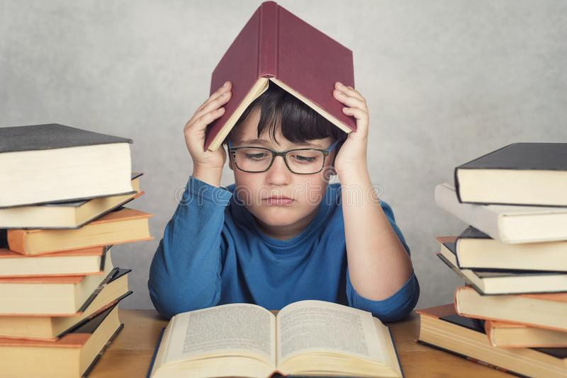 Sad and pensive boy with books on a table stock images