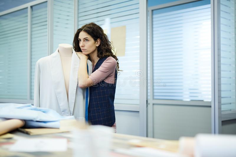 Sad pensive female tailor leaning on mannequin stock image