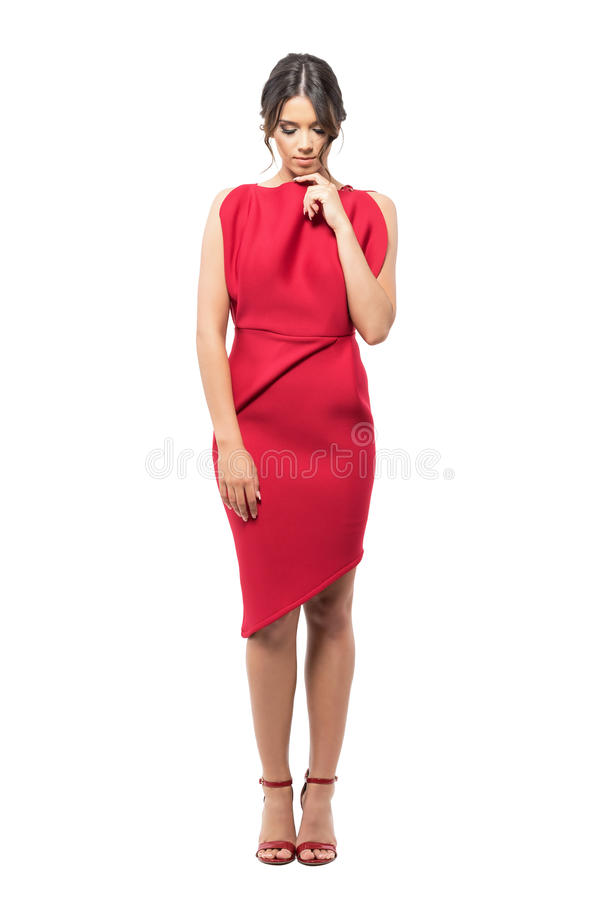 Sad pensive Latin woman in red dress with finger on chin looking down thoughtful. stock photography