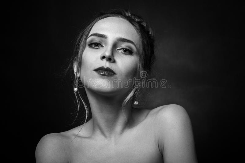 Sad pensive young. Beautiful sad pensive young blond female portrait on black background stock photos
