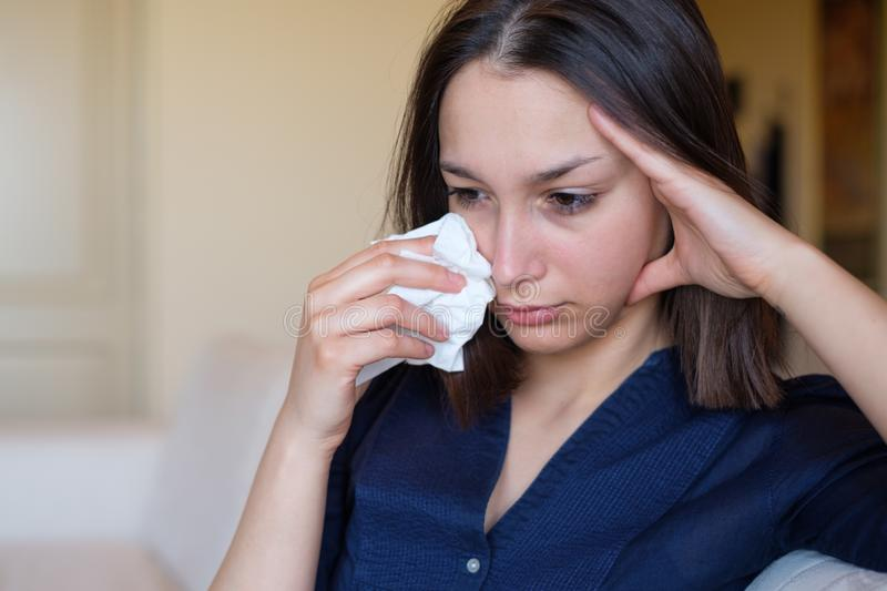 Woman crying on the sofa after relationship breakup stock photo