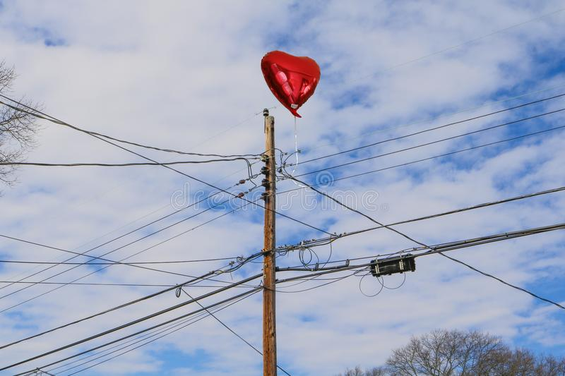Sad photo of red heart balloon stuck on telephone wires stock photo