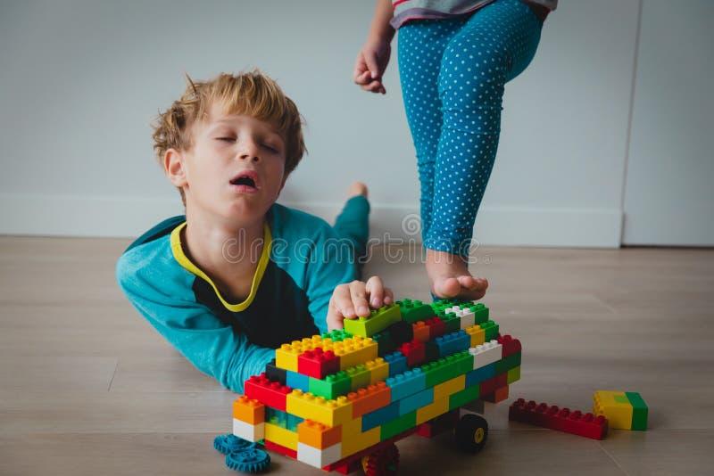 Sad pojke i stress medan syster förstör hans konstruktion, syskon rivalitet arkivbilder