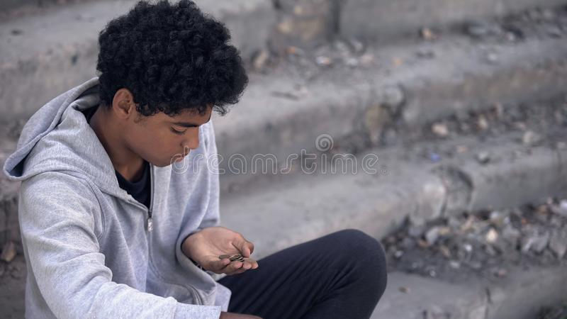 Sad poor teenager looking at coins in hand sitting outdoors, urban unemployment royalty free stock images