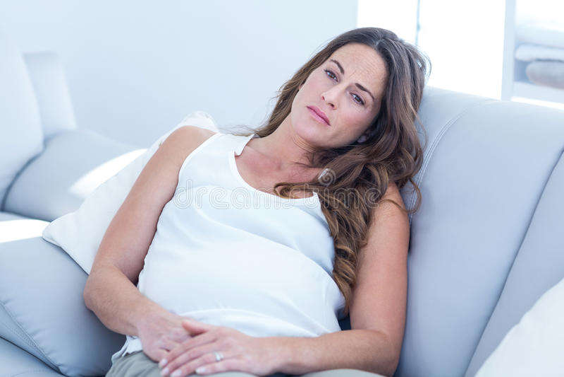 Sad pregnant woman leaning on sofa stock photo
