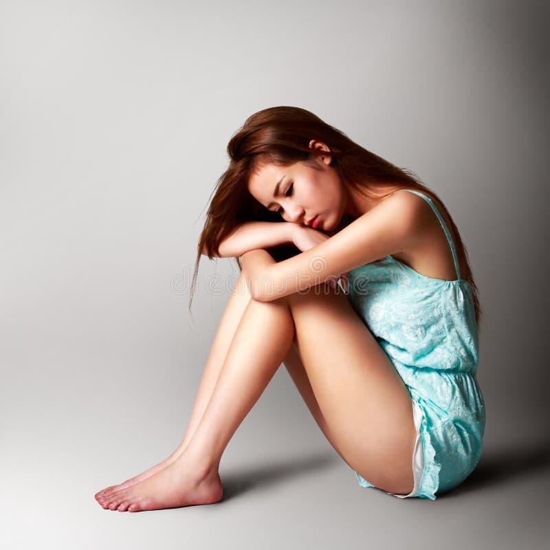 Sad pretty girl sitting on the floor royalty free stock image