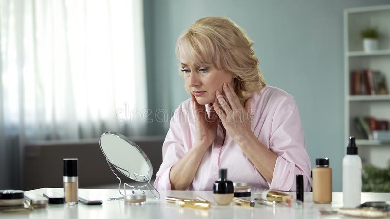 Sad pretty lady looking in mirror, touching her face, anti-wrinkle skin care. Stock photo stock image