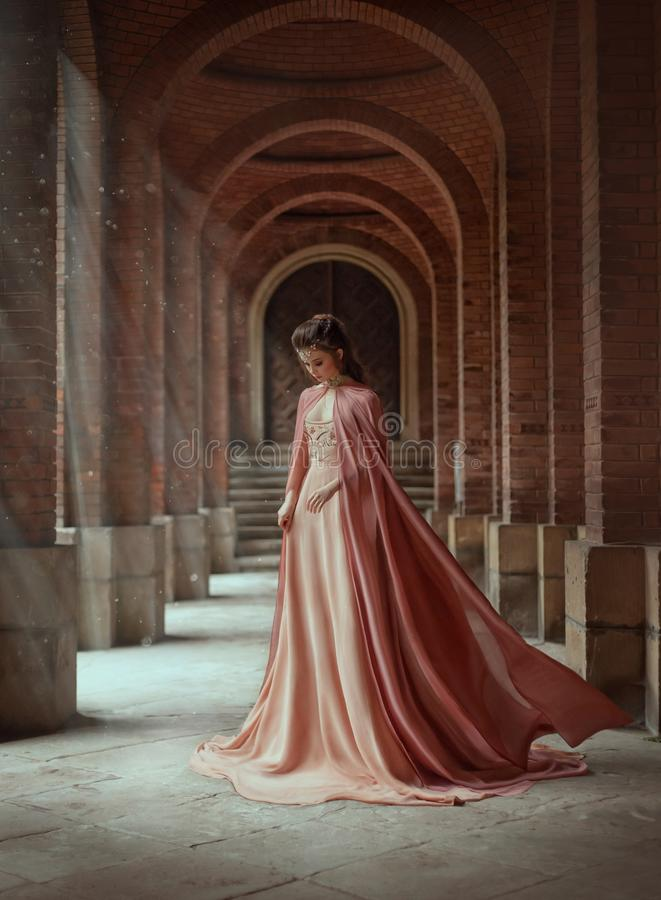 Sad princess in a vintage royal dress and in a cloak that flies in the wind. Sad princess in a vintage royal nude powdery color dress and in a cloak that flies royalty free stock photo