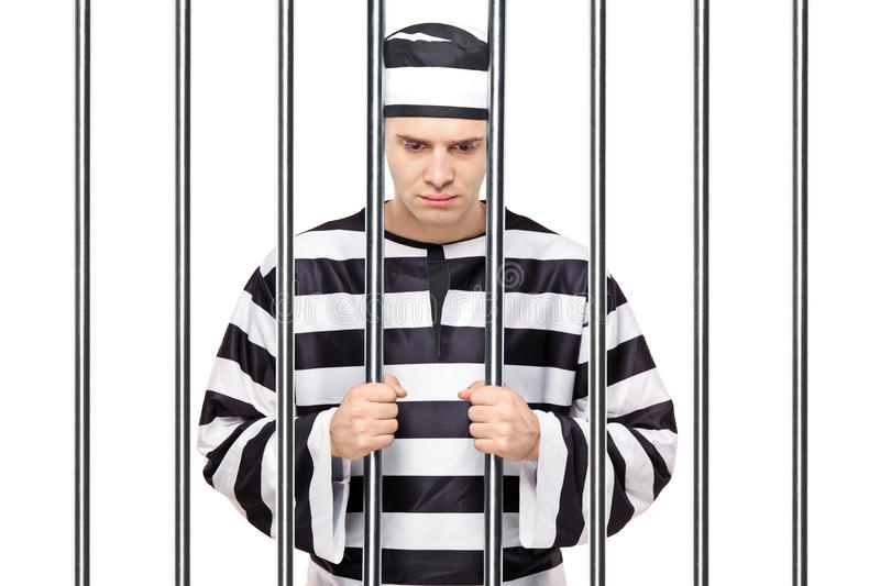 A sad prisoner in jail holding bars. A view of a sad prisoner in jail holding bars isolated on white background