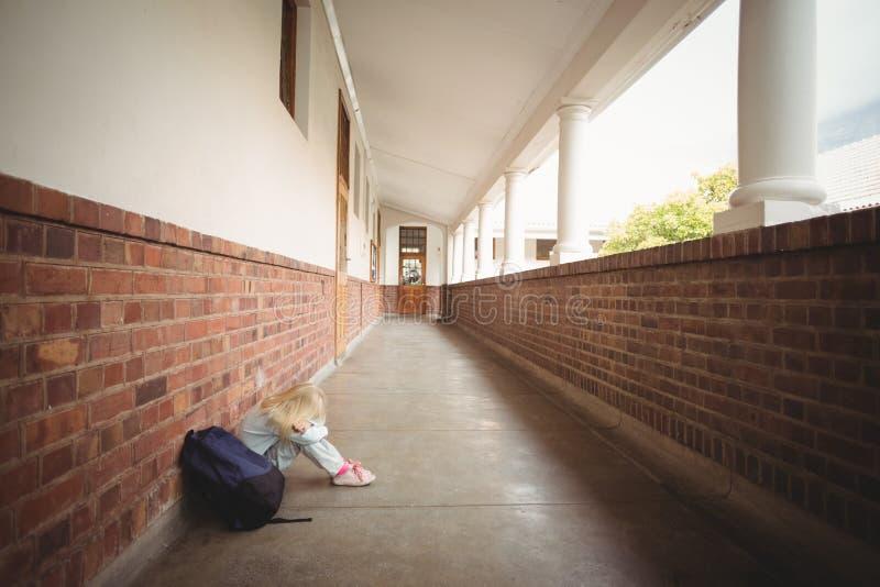 Sad pupil sitting alone on ground. At corridor stock photo