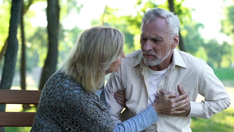 Sad retired man feeling heart pain, cardio problems, wife supporting husband. Sad retired men feeling heart pain, cardio problems, wife supporting husband, stock stock photos