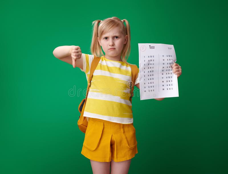 Sad school girl with bad grade test showing thumbs down. Sad school girl with backpack with a bad grade test showing thumbs down isolated on green stock photo