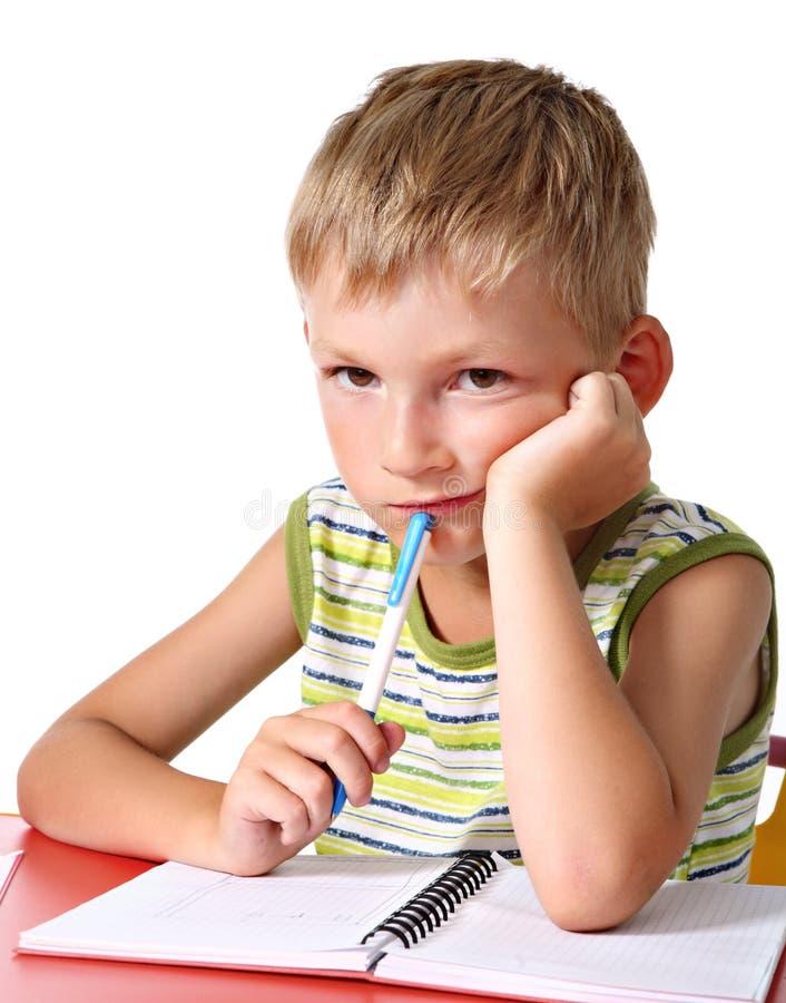 Sad schoolboy doing homework stock images