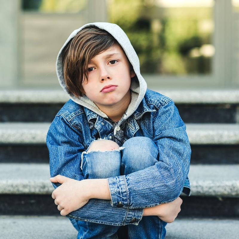 Sad schoolboy sitting alone at stairs outside. Bullying, discrimination and depression concept. Boy in stress. Back to school.  stock photo