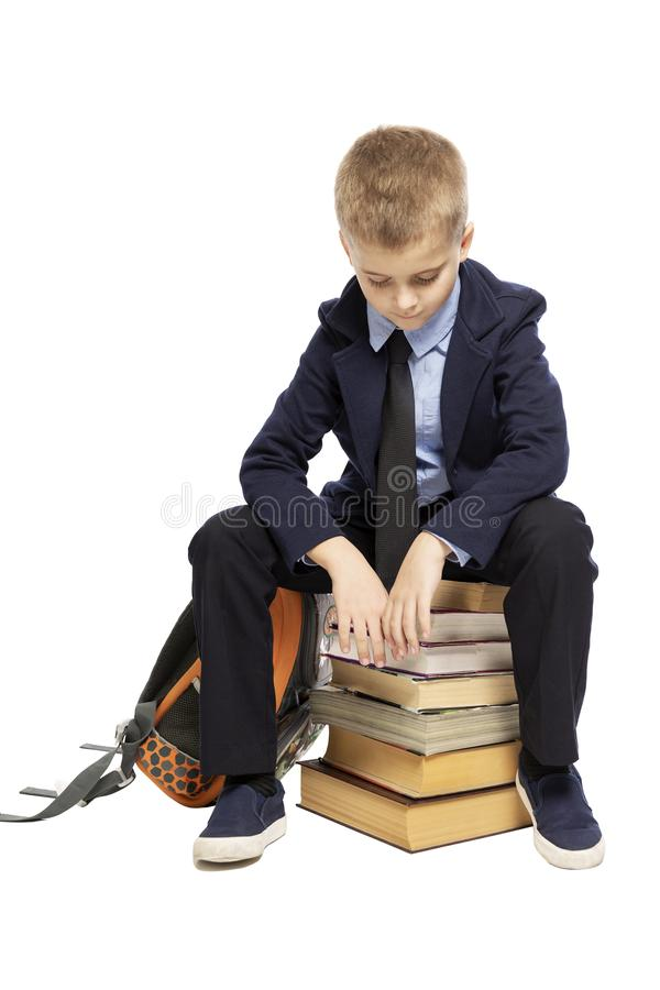 Sad schoolboy in a suit sitting on a pile of books, head bowed. Isolated on a white background. Vertical stock photo