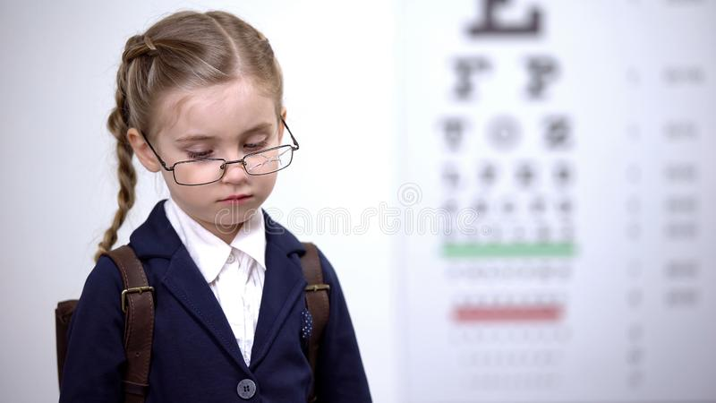 Sad schoolgirl in broken glasses feels insecure, bullied by peers for spectacles. Stock photo royalty free stock image
