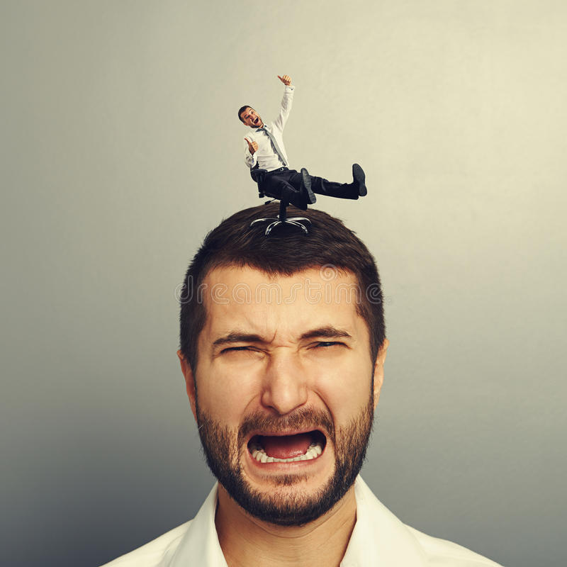Sad screaming man with small happy man. Portrait of sad screaming man with small happy man on the head stock images