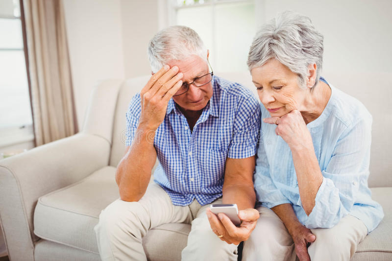 Sad senior couple looking at mobile phone stock image