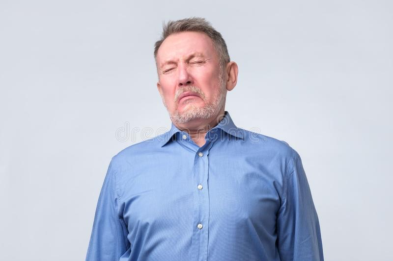 Sad senior man in blue shirt is about to cry. He is tired. Low energy concept. Negative facial emotion at old age royalty free stock photos