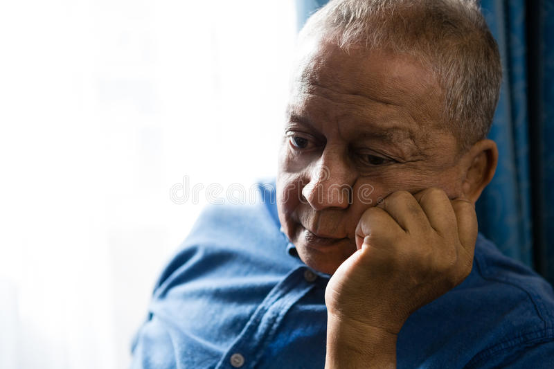 Sad senior man with hand on chin sitting by window. Close up of sad senior man with hand on chin sitting by window royalty free stock image