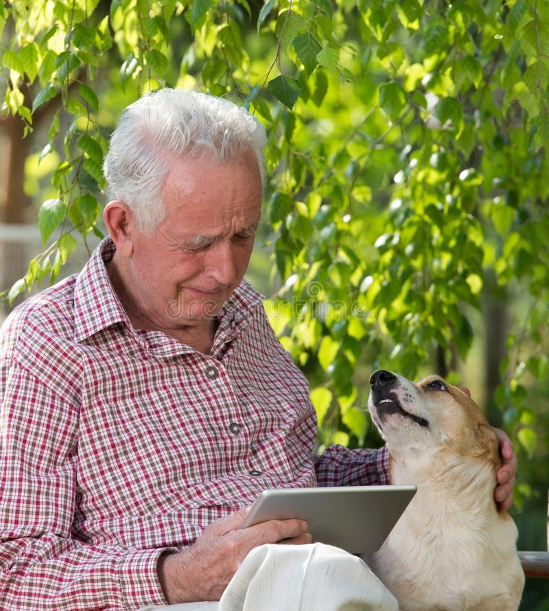Old man with dog and tablet crying in garden stock photography