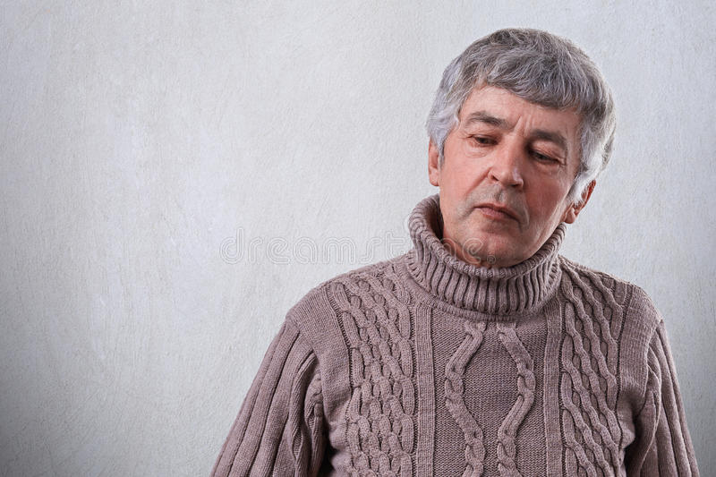 A sad senior man looking thoughtful down dressed in sweater. A wrinlked elderly man with gray hair thinking about his life having stock images