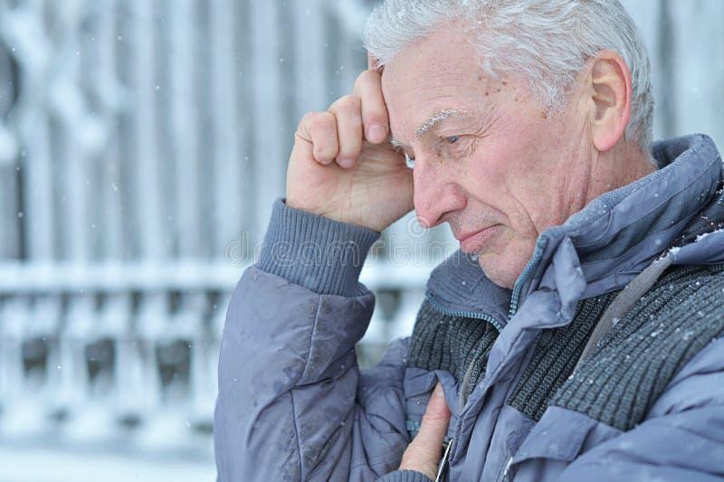 Sad senior man står utomhus på vintern royaltyfria bilder