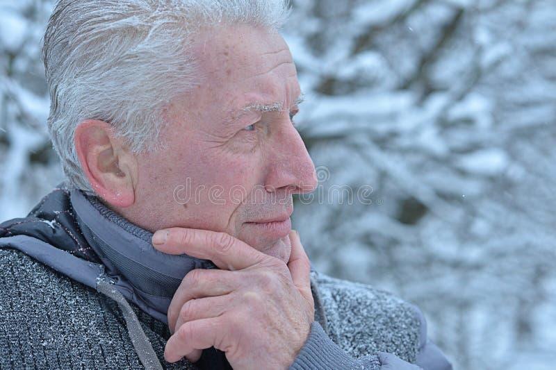 Sad senior man står utomhus på vintern royaltyfri fotografi