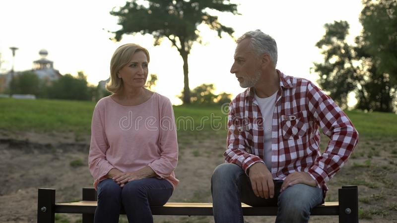 Sad senior man and woman sitting on bench, looking at each other, reconciliation stock photo