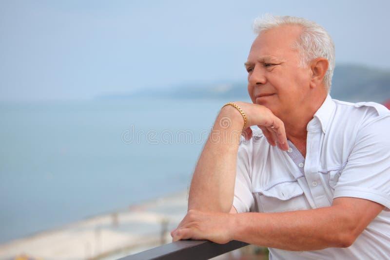 Sad senior on veranda near seacoast, looking afar