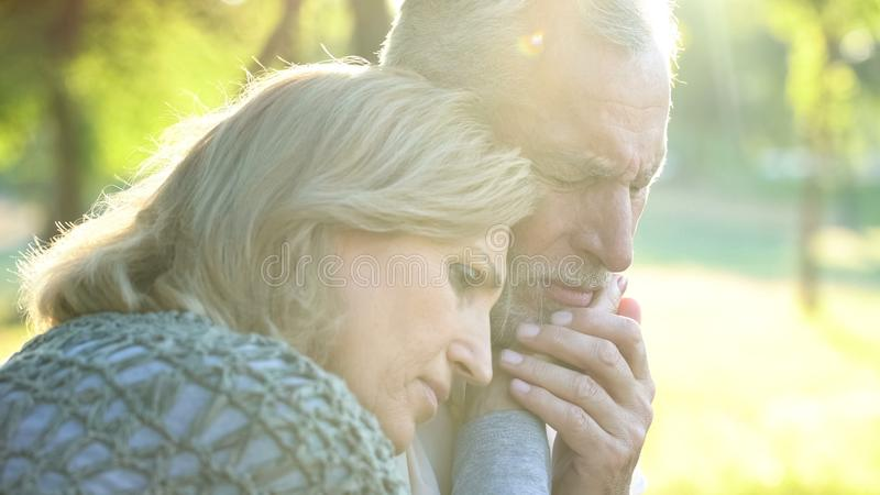 Sad senior wife embracing crying husband, relative loss, grief and sorrow. Stock photo stock images