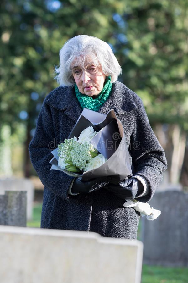 Sad Senior Woman With Flowers Standing By Grave royalty free stock image