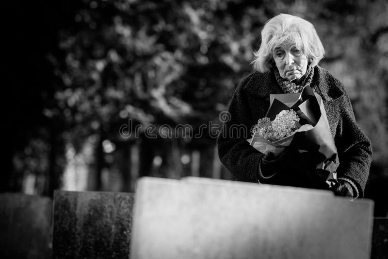 Sad Senior Woman With Flowers Standing By Grave stock image