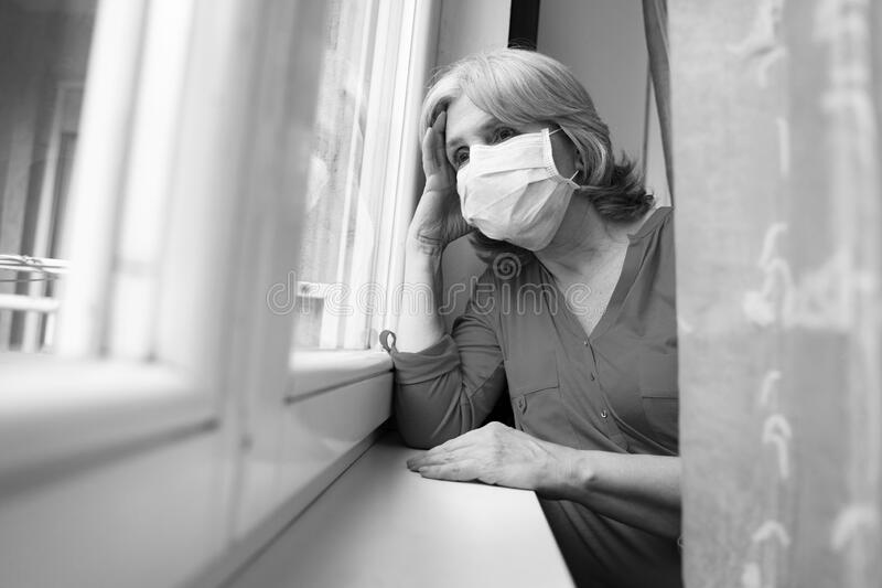 senior woman next to window with mask on face stock photo