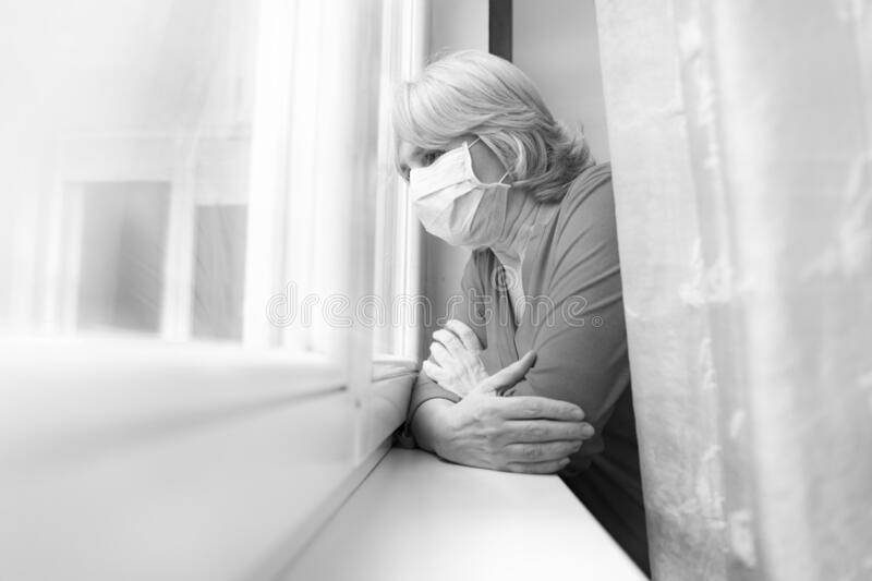 Sad senior woman looking outside her window with mask on face, stock images