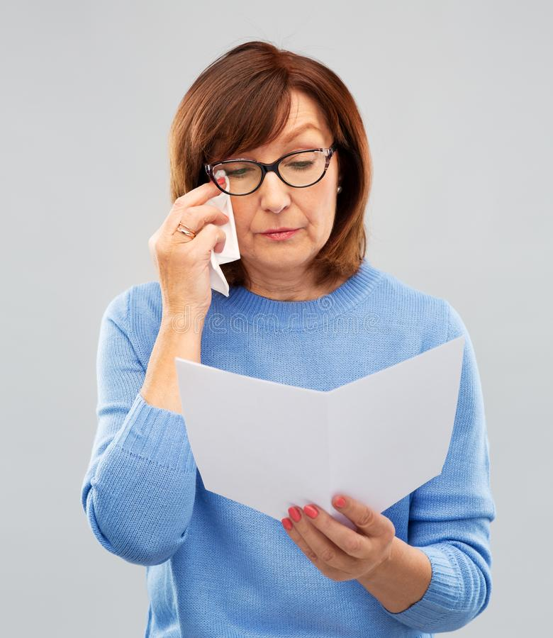 Sad senior woman reading letter and crying royalty free stock photos