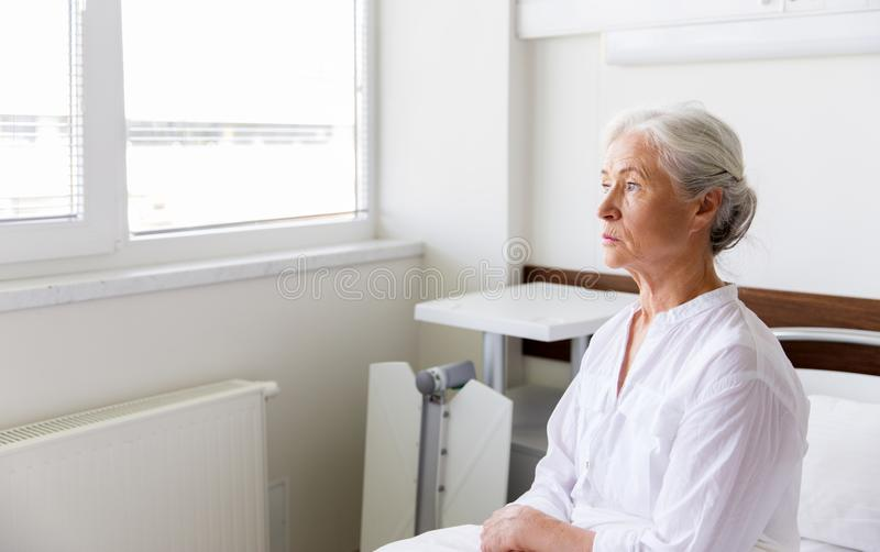 Sad senior woman sitting on bed at hospital ward. Medicine, healthcare and old people concept - sad senior woman sitting on bed at hospital ward stock photos